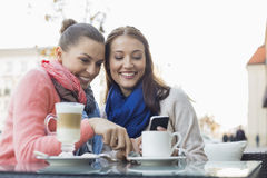 Amigos femeninos felices que usan el teléfono celular en el café de la acera Fotografía de archivo libre de regalías