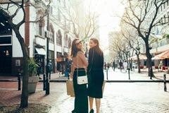 Amigos femeninos hacia fuera para hacer compras en la ciudad Imágenes de archivo libres de regalías