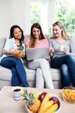 Amigos femeninos hermosos que miran en ordenador portátil en casa Fotografía de archivo