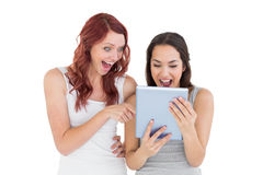 Amigos femeninos jovenes chocados que miran la tableta digital Fotos de archivo libres de regalías