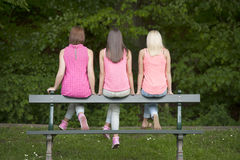 Amigos femeninos jovenes de Hree asentados en un banco, al aire libre Imagen de archivo