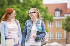 Amigos femeninos jovenes felices de la universidad que caminan al aire libre Imagen de archivo libre de regalías