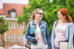 Amigos femeninos jovenes felices de la universidad que caminan al aire libre Imagen de archivo