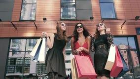 Amigos femeninos jovenes felices que hablan alegre al aire libre después de hacer compras metrajes