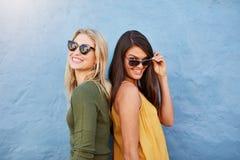 Amigos femeninos jovenes felices que se unen Imagen de archivo libre de regalías