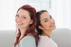 Amigos femeninos jovenes hermosos que se sientan de nuevo a la parte posterior en casa Imágenes de archivo libres de regalías