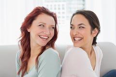 Amigos femeninos jovenes hermosos que se sientan de nuevo a la parte posterior en casa Imagen de archivo libre de regalías