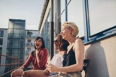 Amigos femeninos jovenes que gozan en terraza fotos de archivo