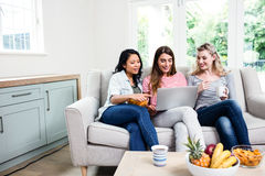 Amigos femeninos jovenes que miran en ordenador portátil en casa Fotos de archivo libres de regalías