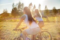 Amigos femeninos jovenes que montan las bicis en luz del sol Imágenes de archivo libres de regalías