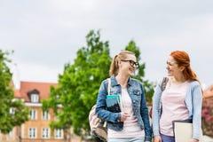 Amigos femeninos jovenes sonrientes de la universidad que caminan al aire libre Fotos de archivo