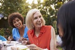 Amigos femeninos maduros que disfrutan de la comida al aire libre en patio trasero imagen de archivo libre de regalías