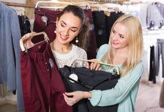 Amigos femeninos positivos jovenes felices que eligen los pantalones Fotografía de archivo