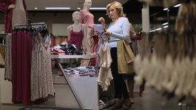 Amigos femeninos positivos que eligen la ropa en tienda metrajes