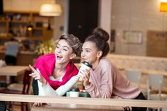 Amigos femeninos que almuerzan en el café de la alameda que ríe y que sonríe después de hacer compras imágenes de archivo libres de regalías