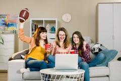 Amigos femeninos que animan a la liga del deporte, f?tbol de observaci?n junto en casa Las tres mujeres emocionales en el reloj a fotos de archivo libres de regalías