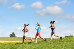 Amigos femeninos que corren el prado soleado en declive Imagenes de archivo