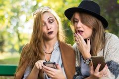 Amigos femeninos que cotillean con el teléfono en el parque Fotos de archivo libres de regalías