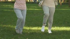 Amigos femeninos que hacen ejercicio de la aptitud afuera, pérdida de peso, retiro activo almacen de metraje de vídeo