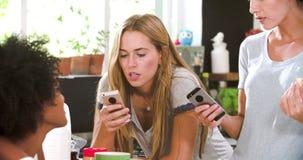 Amigos femeninos que hacen el desayuno mientras que comprueba el teléfono móvil almacen de video