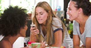 Amigos femeninos que hacen el desayuno mientras que comprueba el teléfono móvil almacen de metraje de vídeo