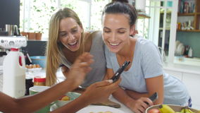 Amigos femeninos que hacen el desayuno mientras que comprueba el teléfono móvil metrajes