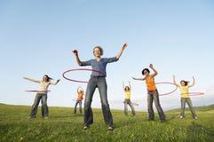 Amigos femeninos que juegan con el aro de Hula contra el cielo en parque Fotos de archivo libres de regalías