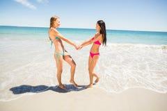 Amigos femeninos que llevan a cabo las manos en la playa Imagen de archivo libre de regalías