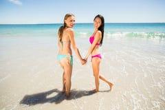 Amigos femeninos que llevan a cabo las manos en la playa Fotos de archivo libres de regalías