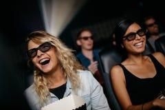 Amigos femeninos que miran la película 3d y la risa foto de archivo libre de regalías
