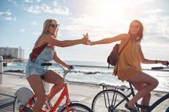 Amigos femeninos que montan ciclos y que se divierten Fotografía de archivo libre de regalías