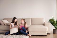 Amigos femeninos que se relajan en sala de estar con los teléfonos Imagen de archivo