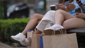 Amigos femeninos que se sientan al aire libre con los bolsos de compras almacen de metraje de vídeo