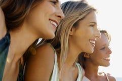 Amigos femeninos que sonríen mientras que mira lejos Fotografía de archivo