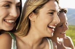 Amigos femeninos que sonríen mientras que mira lejos Foto de archivo
