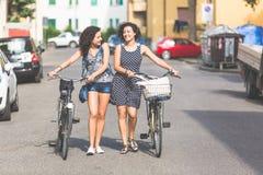 Amigos femeninos que sostienen las bicis y que caminan en la ciudad Fotografía de archivo