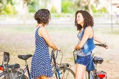 Amigos femeninos que sostienen las bicis y que caminan en la ciudad Imágenes de archivo libres de regalías