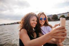 Amigos femeninos que toman el selfie con el teléfono móvil por el lago Imagenes de archivo