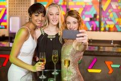 Amigos femeninos que toman el selfie del teléfono móvil mientras que comiendo champán Fotos de archivo