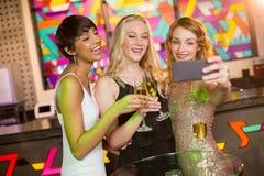 Amigos femeninos que toman el selfie del teléfono móvil mientras que comiendo champán Imagenes de archivo