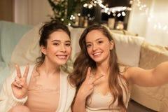 Amigos femeninos que toman el selfie en casa Imágenes de archivo libres de regalías
