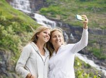 Amigos femeninos que toman el selfie en una cascada de la montaña Fotografía de archivo libre de regalías
