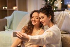Amigos femeninos que toman el selfie por smartphone en casa Foto de archivo