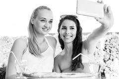 Amigos femeninos que toman un selfie con smartphone Fotos de archivo