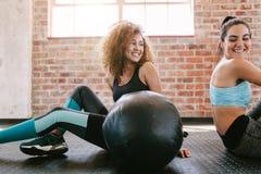 Amigos femeninos que toman una rotura del entrenamiento en gimnasio fotografía de archivo libre de regalías