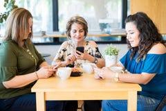 Amigos femeninos que usan los teléfonos móviles en el café fotos de archivo