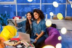 Amigos femeninos sonrientes que hacen la fotografía del autorretrato Imágenes de archivo libres de regalías