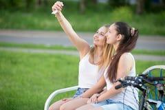 Amigos femeninos sonrientes que toman el selfie en parque Imagen de archivo libre de regalías