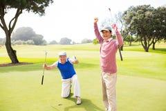Amigos Golfing que cheering no verde de colocação Imagens de Stock
