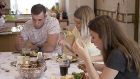 Amigos hambrientos adolescentes que se unen en la cocina en la tabla que disfruta de una consumición malsana de buen gusto del al metrajes